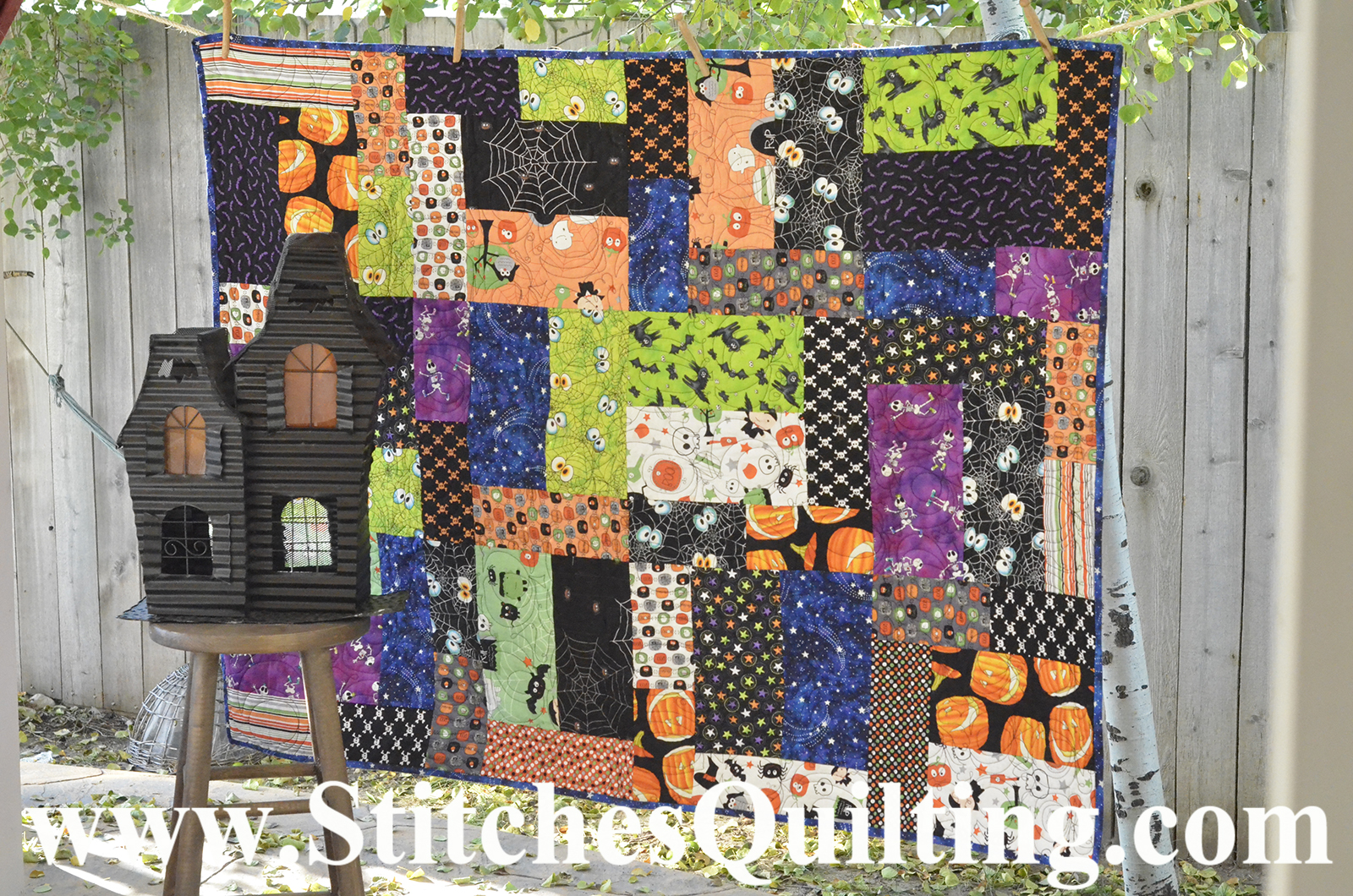 I love fabric and here is a playfully bright quilt that I made with fabrics collected through the years. I just love my antique cloths pins that this quilt is hung on. Can you see the pumpkins that I long arm quilted into the layers!