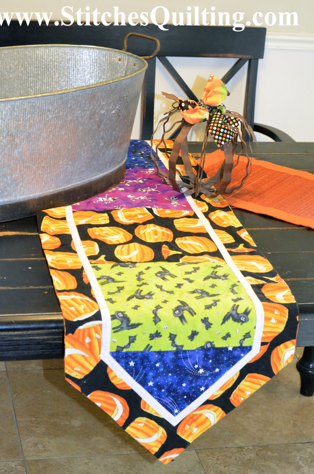 Setting up tables with Halloween settings that include bright Halloween fabric table runners. This table runner was so simple to make with basic squares and actually has no batting in it so it is sewn like pillow case and then turned inside and out.