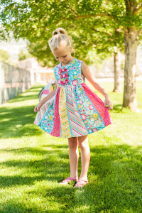 I'm dying to make this bright happy dress!  Look at those fabrics and personalized touches!