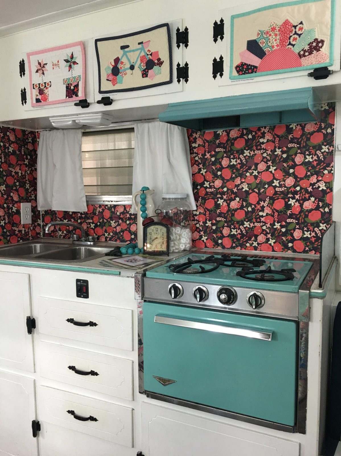 Look at the retro kitchen, Carina's designed Posy Garden Wallpaper and the aqua blue oven! Her cute family actually camps in this and everything works!